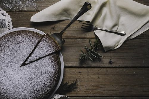 A chocolate cake is being served on a wooden table, decorated with herbs.