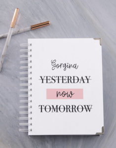"A white wire ring bound personalised notebook with the words ""yesterday"" and ""tomorrow"" are crossed out while the word ""now"" is highlighted in light pink."